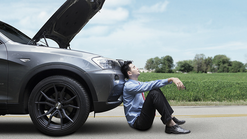 Young businessman waiting a help while sitting on the road with broken car